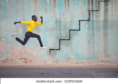 Afro man in yellow shirt jumping in front of a blue wall