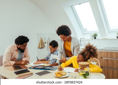 Afro parents assisting their son and daughter with schoolwork at home