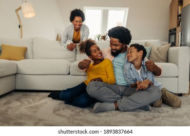 Afro parents and children having fun and smiling while spending weekend at home