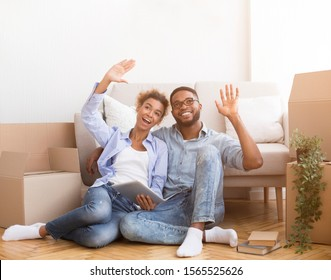 Afro Spouses Using Digital Tablet Sitting Among Moving Boxes Indoor Discussing Renovation And Interior Design For New House.