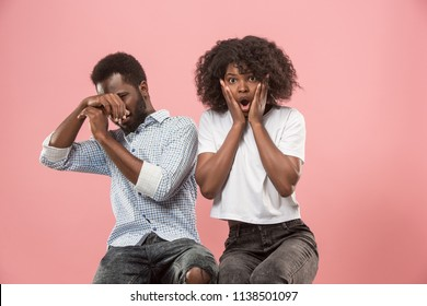The afro surprised couple watching sports match on tv at home, successful game. Different emotions concept. Studio shot with african american man and woman