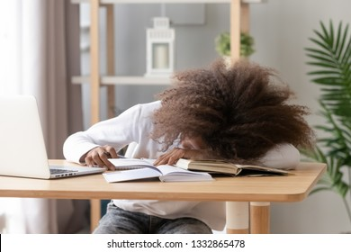 Afro teen schoolgirl sitting at home or classroom lying on desk filled with books training material and notebook schoolchild sleeping lazy bored to study lack of energy fatigue during learning concept