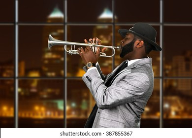 Afro trumpeter's performance at night. Musician in city concert hall. Gifted trumpet player. Stylish musician with a trumpet.