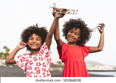 Afro twins sisters running on the beach while playing with wood toy airplane - Main focus on right kid face