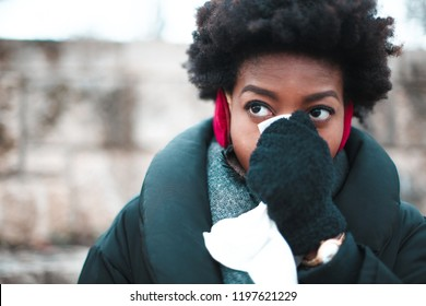 Afro woman blowing her nose in winter on the street.