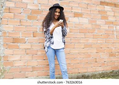 afro woman with hat with mobile phone on the brick wall