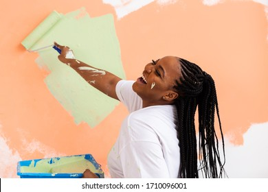 Afro woman painting the walls of new home. Renovation, repair and redecoration concept.