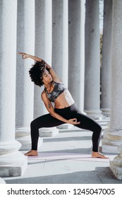 Afro woman practicing yoga in the city