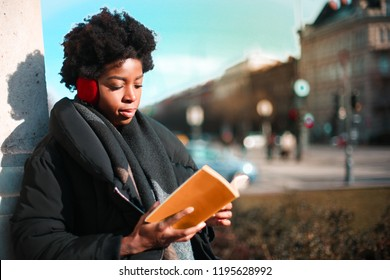 Afro woman reading a book on the street.