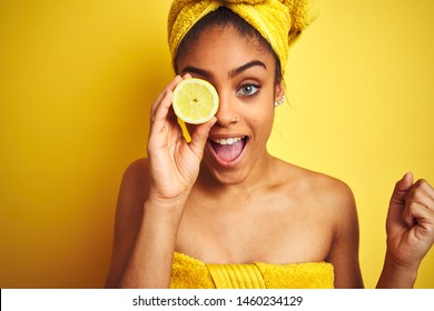 Afro woman wearing towel after shower holding slice lemon over isolated yellow background screaming proud and celebrating victory and success very excited, cheering emotion