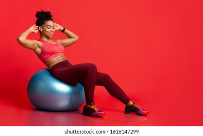 Afro woman working out with fitness ball, doing exercises for muscle press over red background, panorama with copy space