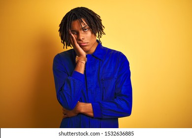 Afro worker man with dreadlocks wearing mechanic uniform over isolated yellow background thinking looking tired and bored with depression problems with crossed arms.