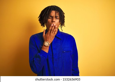 Afro worker man with dreadlocks wearing mechanic uniform over isolated yellow background bored yawning tired covering mouth with hand. Restless and sleepiness.