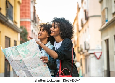 Afro Young Mother Using a Map with her Daughter . Mother and Daughter on Vacations or Holidays in Europe . Afro American Sisters Looking an Address in the Street. Holidays Concept.