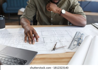 Afro-amerikanischer Architekt arbeitet im Büro mit blueprints.Engineer inspiziert Architekturplan, Skizze eines Bauprojekts. Porträt eines schwarz-gut aussehenden Mannes, der am Arbeitsplatz sitzt. Geschäftskonzept.