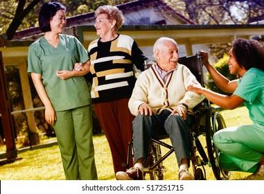 Afroamerican and asian nurses joking with elder people in hospital garden.