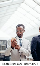 afroamerican bearded Businessman wearing suit and glasses texting on phone in mall or hall of modern office. Business Concept