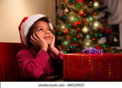 Afroamerican boy near Christmas present. Black kid beside Christmas present. Wait until it's time. Holiday for everyone.