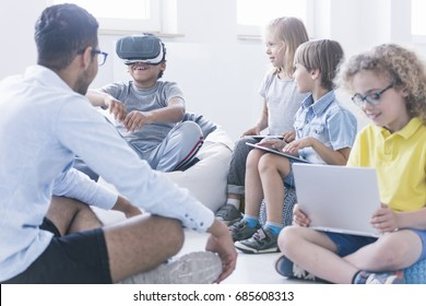Afro-american boy uses VR glasses during information technology lesson