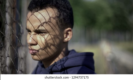 Afro-american boy watching rich district through fence, poverty, immigration