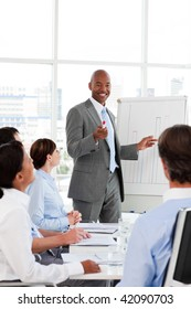 Afro-American businessman introducing stock market to his team in the office