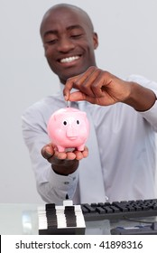 Afro-American businessman saving money in a piggybank in the office