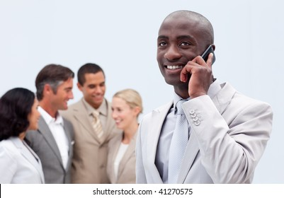 Afro-American businessman talking on mobile phone with his team in the background