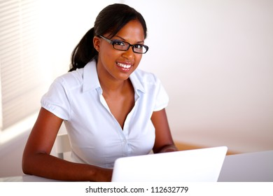 Afro-american businesswoman looking at you in front of her laptop - copyspace