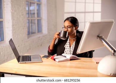 Afroamerican businesswoman sitting by the table in her officce and drinling coffee or tea.