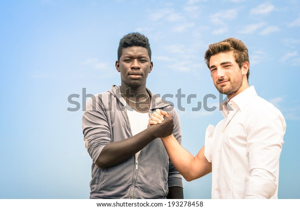Afroamerican and caucasian men shaking hands in a modern handshake to show each other friendship and respect - Arm wrestling against racism on a blue sky