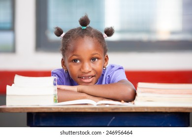 Afroamerican elementary student happy with books on her desk.