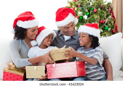 Afro-American family holding Christmas gifts at home