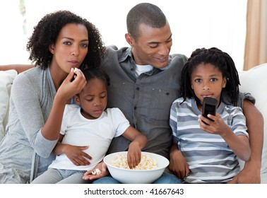 Afro-American family watching a film at home and earting popcorn