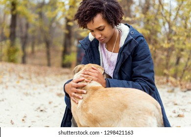 afroamerican girl in autumn park playing with her dog