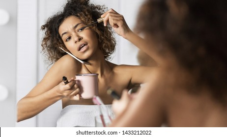 Afro-american girl in hurry put on makeup, drinking coffee and talking by phone simultaneously in front of mirror in bathroom. Sorry, I am late today concept