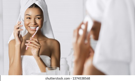 Afro-american girl talking by phone and cleaning teeth simultaneously in front of mirror in bathroom. Morning rush concept