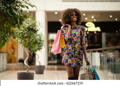 Afro-american girl walking and smiling with a lot on shopping bags.