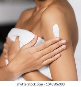 Afro-american girl's hand applying cream on her shoulder. Collagen body butter concept
