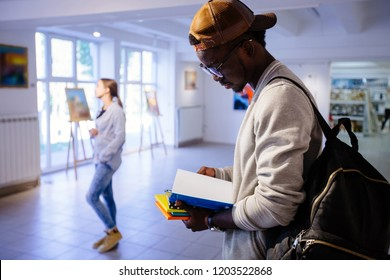Afro-american hipster student man in eyeglasses with backpack holding colorful stack of books, reading one of book. Guy in art gallery. Multi ethnic, study abroad, culture concept.