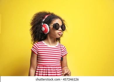 Afro-American little girl with headphones listening to music on yellow background