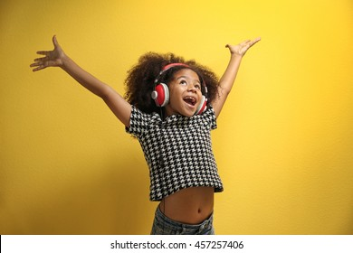 Afro-American little girl with headphones on yellow background