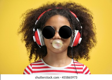 Afro-American little girl with headphones and sunglasses chewing gum on yellow background