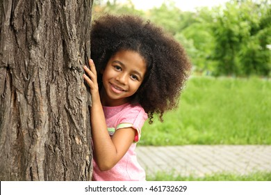 Afro-American little girl hiding behind tree in park