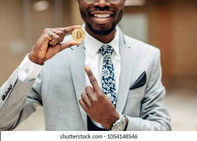 afroamerican man wearing suit holding golden bitcoin, e-money ,cryptocurrency and online payment concept, selective focus