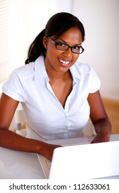 Afro-american secretary looking at you in front of her laptop at workplace