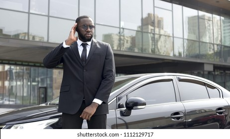 Afro-American security worker listening boss directions in earphones, security