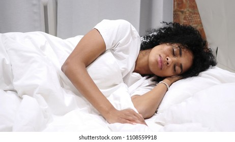 Afro-American Woman in Bed Browsing on Smartphone at Night