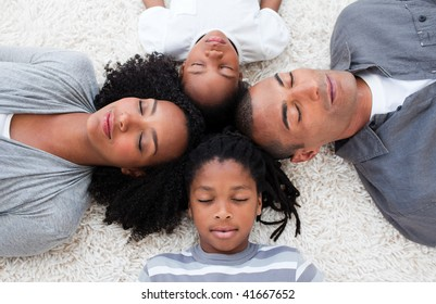 Afro-American young family lying on floor with their heads together