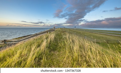 Afsluitdijk dutch dike with fence motorway and cycling track during  sunset with clouded sky