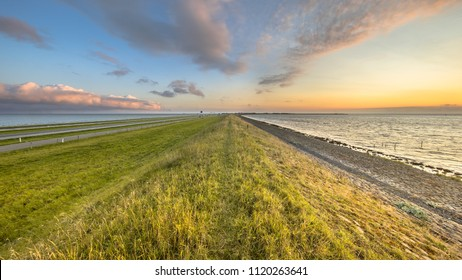 Afsluitdijk dutch dike with motorway and cycling track landscape during sunset with clouded sky